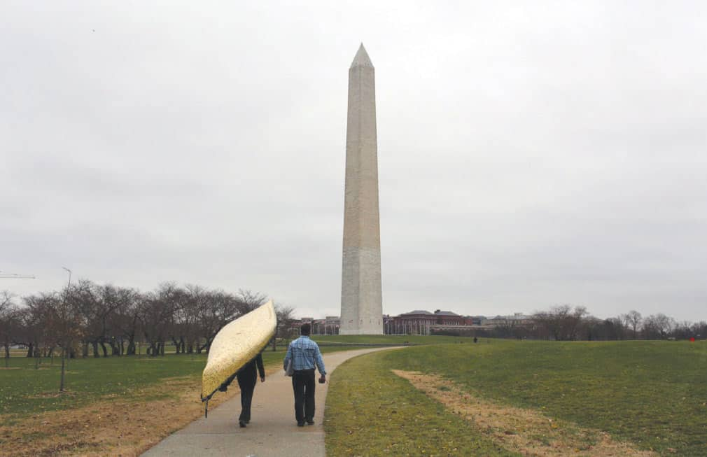 """Dave and Amy Freeman portage their canoe """"Sig"""" in front of the Washington Monument, photo by Nate Ptacek"""