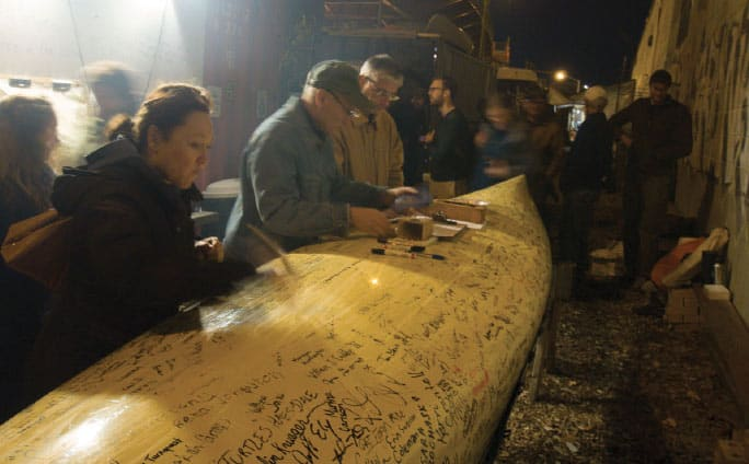 Attendees at a Paddle to D.C. event at the North Brooklyn Boat Club in New York City sign their names on the Freemans' canoe