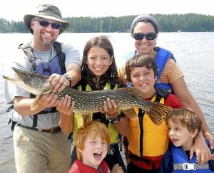 Joseph Goldstein, 13 (center, holding northern pike) is in Washington this week lobbying government officials against copper mining near the BWCAW. He's pictured here in a photo form last summer with Ely guide Jason Zabokrtsky, left, his mother, Kemia Sarraf, right, and his little brothers Jacob, Jonah and Joshua. (Photo by Jeff Goldstein)