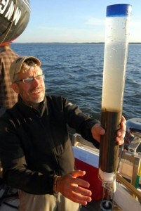 Scientist Mark Edlund recovers a short gravity core from Buffalo Bay, Lake of the Woods