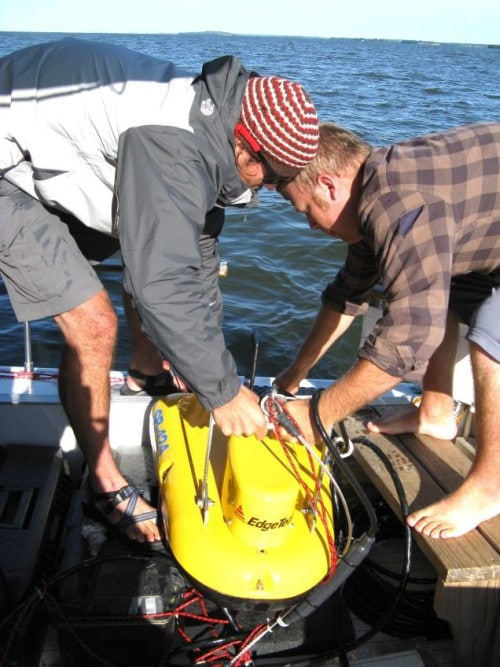 Devin Hougardy and Aaron DeRusha deploy the towfish used to take seismic profiles of the lake bottom. (Photo by Mark Edlund)