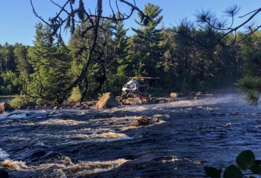 firefighters attaching tether to state patrol helicopter