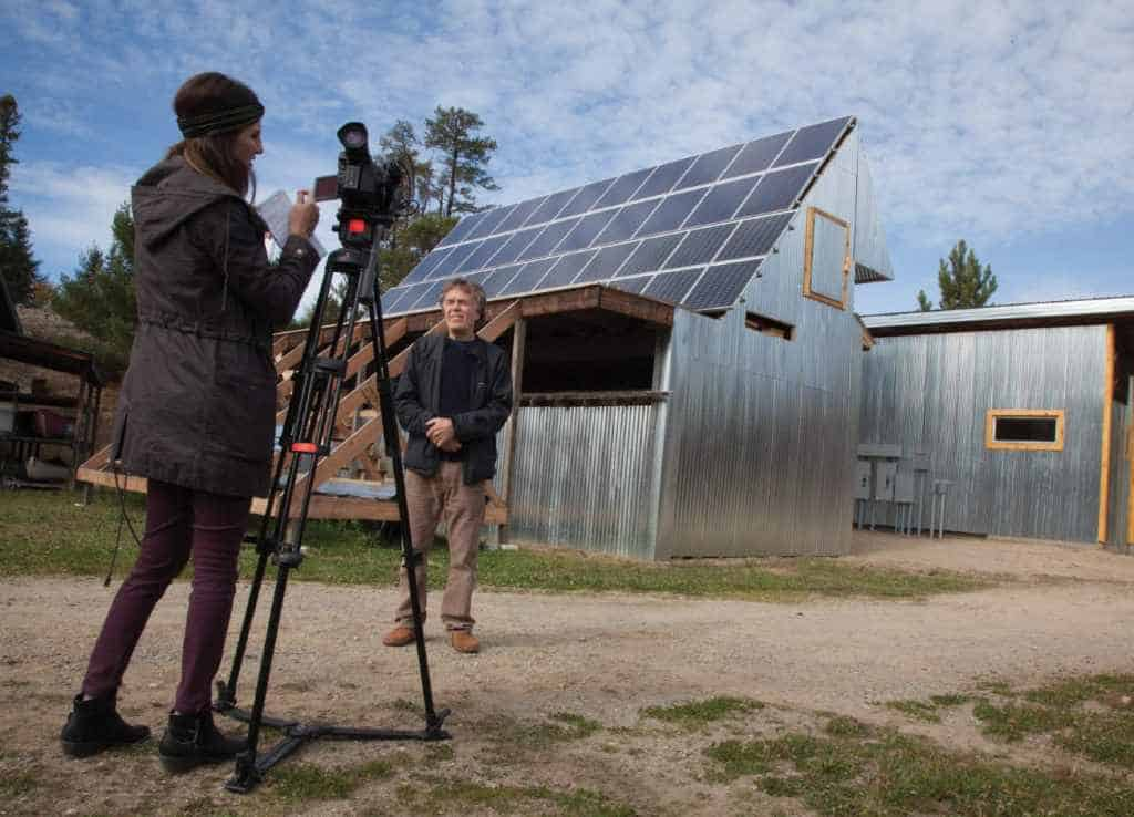 Polar explorer Will Steger being interviewed and photographed by media in front of the newly installed solar array at the Steger Wilderness Center. This is the first micro-grid up and running in Minnesota. Photo by John Ratzloff.