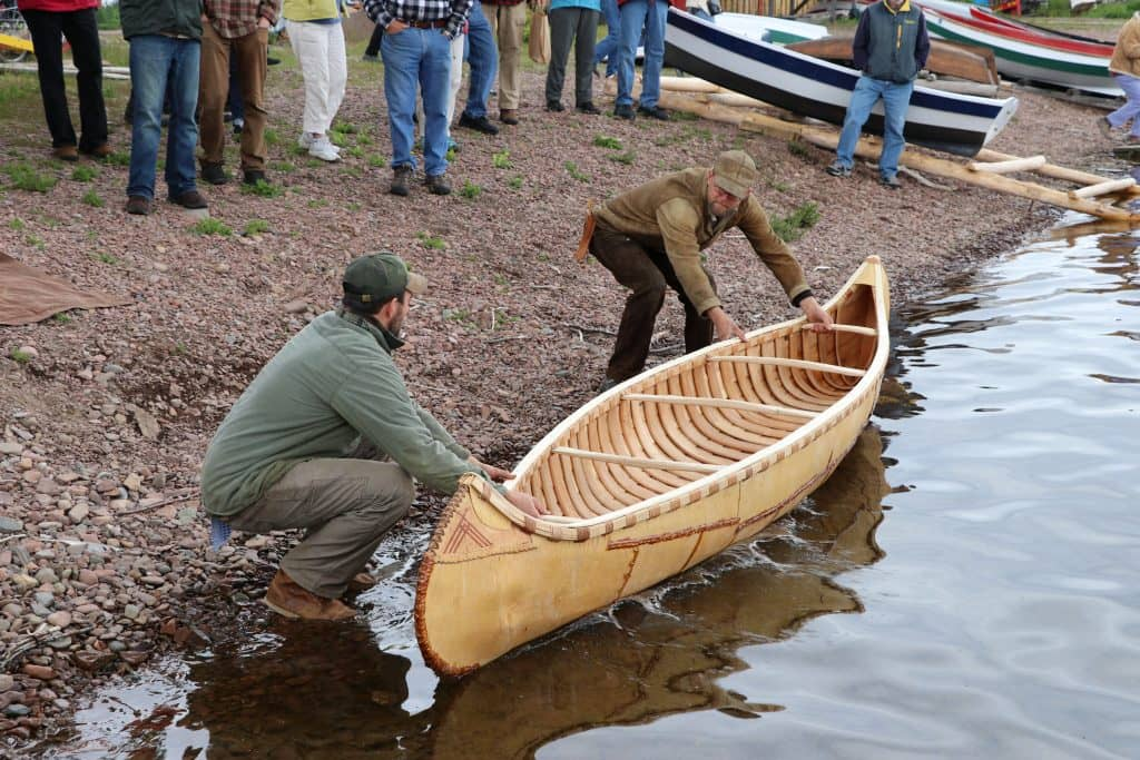 Craftsmen at the North House Folk School launch a handmade birch bark canoe in honor of the school's 20th anniversary. <br>Photo courtesy the North House Folk School.