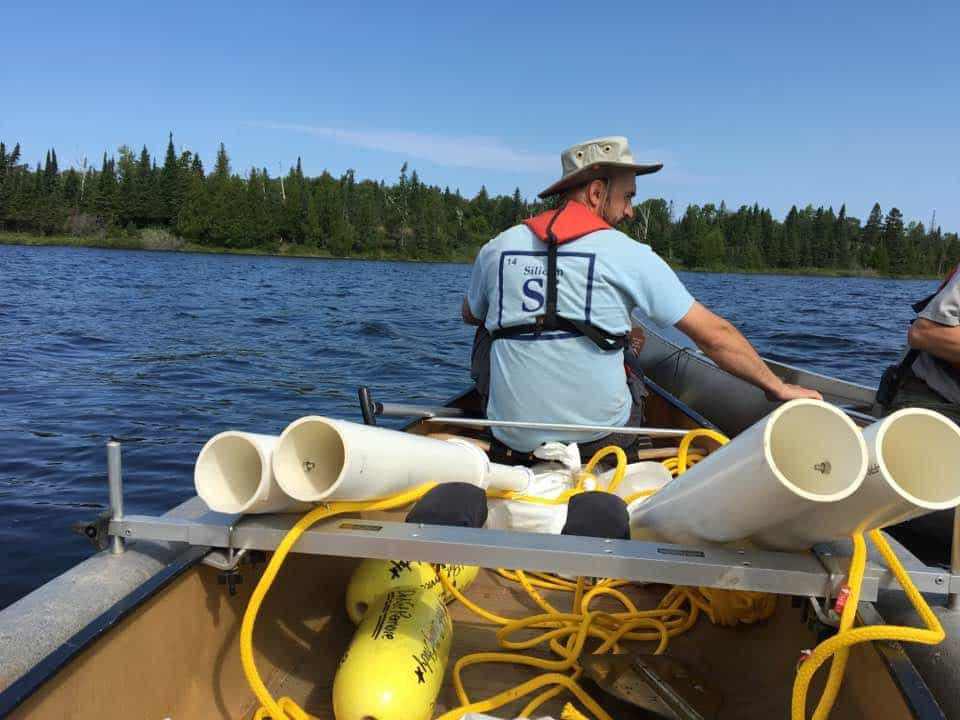 Researcher and University of Minnesota graduate student David Burge paddles a canoe laden with sediment traps on Isle Royale. (Mark Edlund)