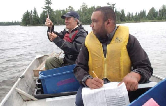 Dakota Lands, Lac La Croix First Nation Fisheries Technician, and Brian Jackson, Quetico Provincial Park Biologist, sample fish populations on Minn Lake in Quetico to assess trends in fish populations. Photo by Conrad Jourdain.