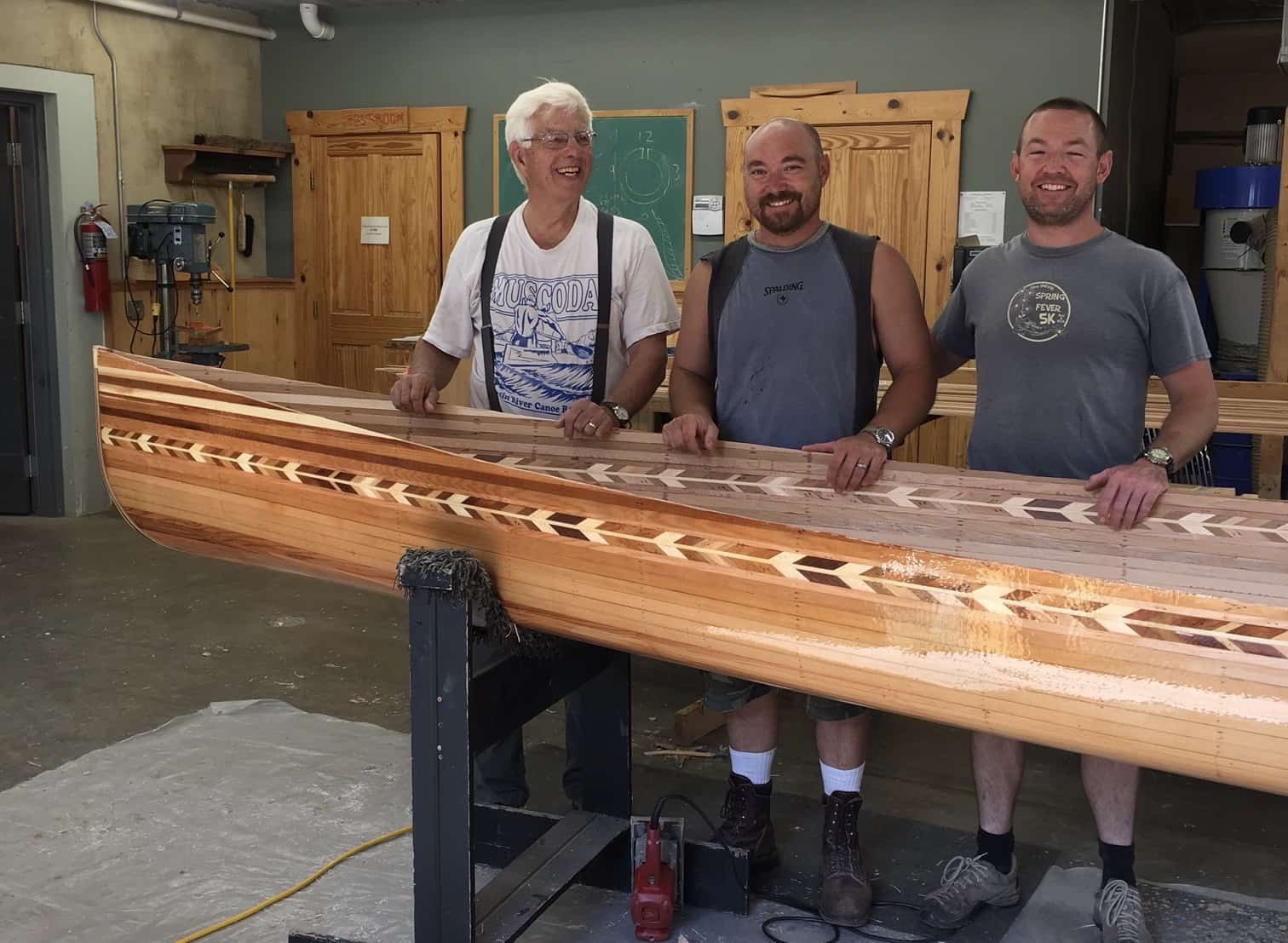 Ken Koscik and two of his students with a wood strip canoe they are building. Photo courtesy Ken Koscik.
